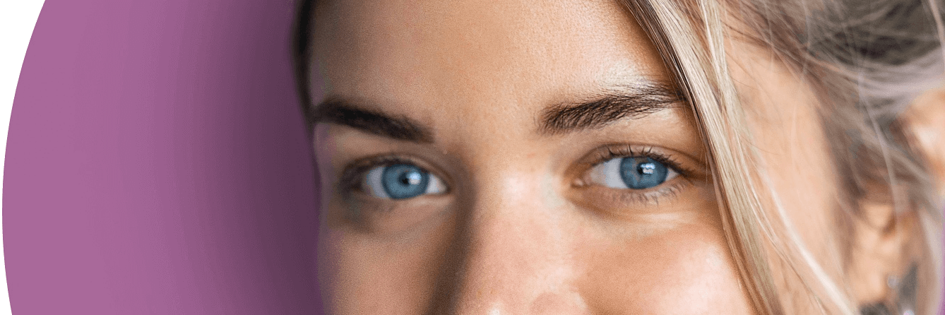 A close up of a person with beautiful blue eyes looking straight.