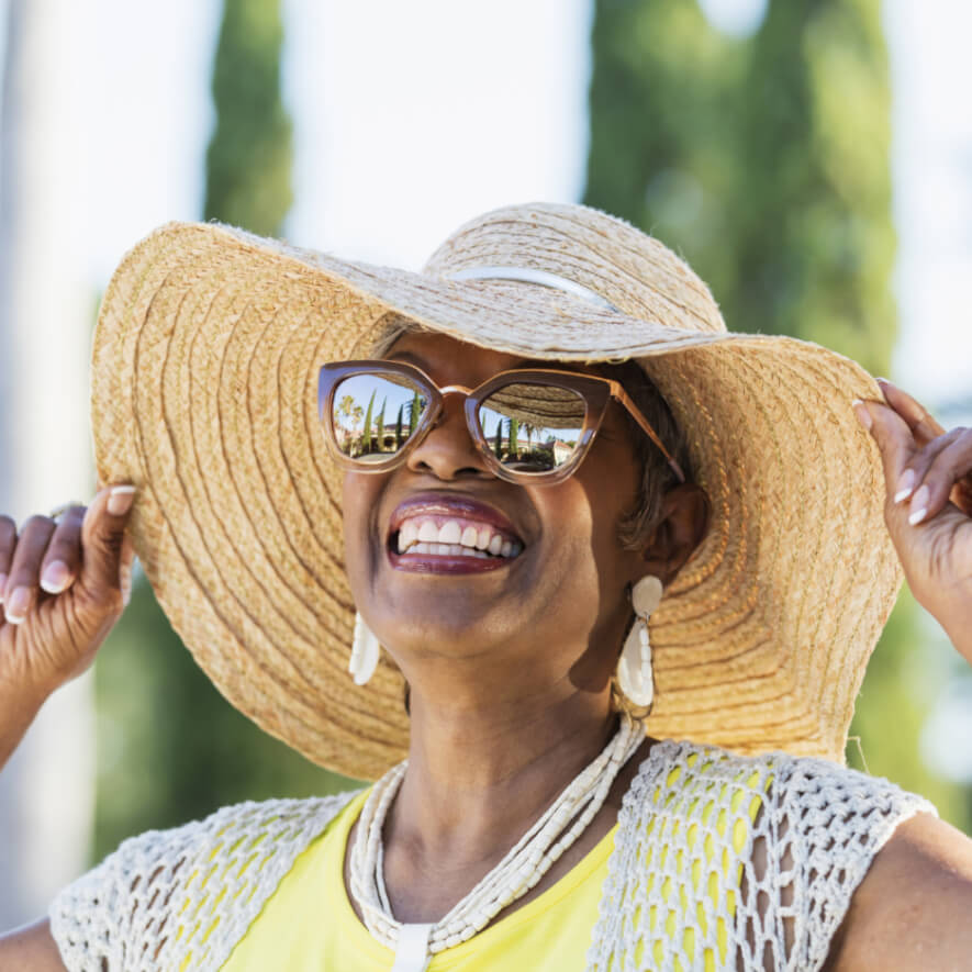 Person in their 60's wearing sunglasses and a wide brim hat on a sunny day, looking up at the sky, smiling.