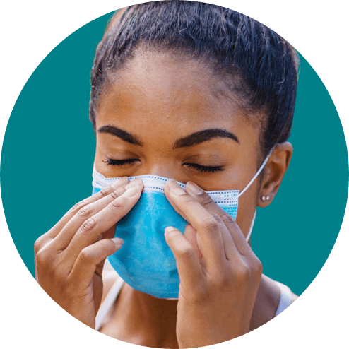 A person closing their eyes while securing a face mask tightly across their nose.